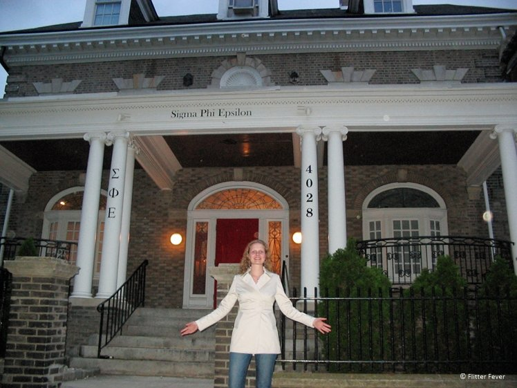 Happy looking lady with her arms wide spread in front of a pretty Sigma Phi Epsilon faternity house in Phladelphia
