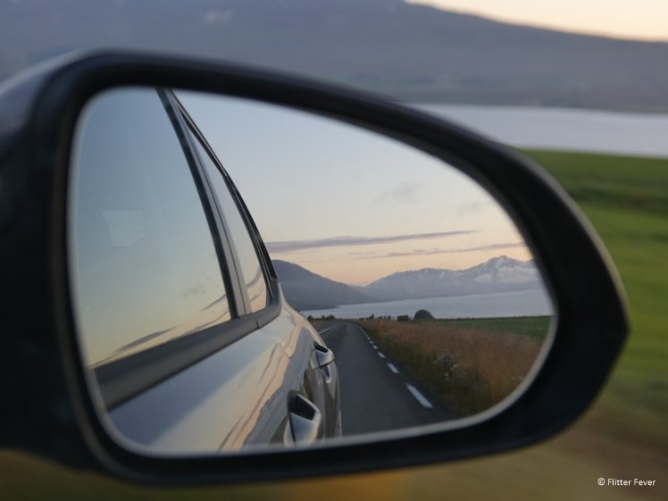 Mirror of car reflects Icelandic landscape at sunset