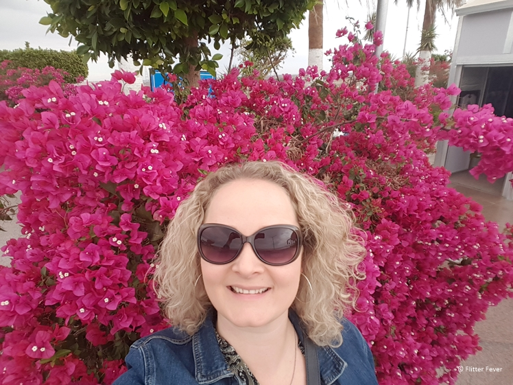 Woman makes selfie at gorgeous pink bougainvillea flowers at Aswan High Dam