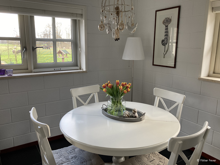Dining table with tulips and a view at B&B Efkesutfanhuzje Hoornsterzwaag